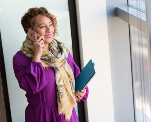 Frau mit Lila Oberteil am Handy